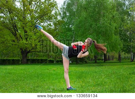 Beautiful kick boxing girl carries a high kick. Outdoors. in the park.
