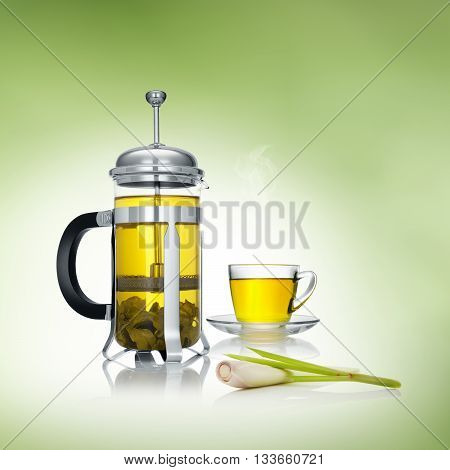 close up view of french press and a cup of green tea on green background