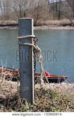 Small rowing boat moored to concrete pole on a natural ground
