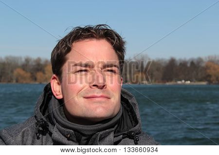 Man relaxing on lakesite facing the sun eyes closed