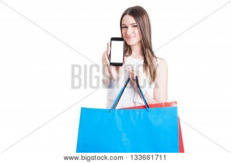 Happy Shopper With Shopping Bags Showing A Blank Smartphone Screen