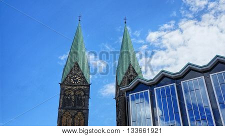 Bremen, Germany. Parliament of Bremen (German: Bremische B rgerschaft) and towers of the Bremen Cathedral (German: 'Bremer Dom') on a sunny day. Partly cloudy sky mirrored in the huge glass front of the government building.