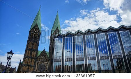 Bremen, Germany. Parliament of Bremen German: Bremische B rgerschaft and towers of the Bremen Cathedral (German: 'Bremer Dom') on a sunny day. Partly cloudy sky mirrored in the huge glass front of the government building.