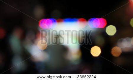 Unfocused scene of people standing front of an illuminated food booth