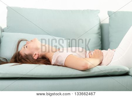 Young Woman In Pain Lying On Couch At Home. Casual Style Indoor Shoot