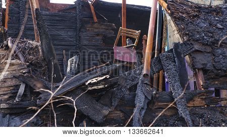 Remains of a burned down house. Old chair hanging above burned boards, planks and other wooden material of a house.