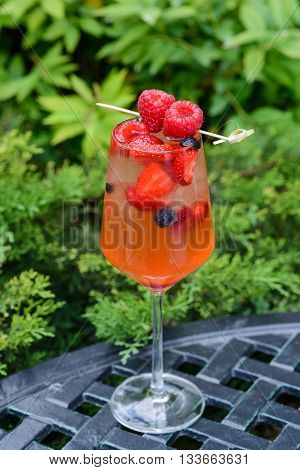 Glass of cold fruit cocktail, with pieces of raspberry, strawberry and ice.