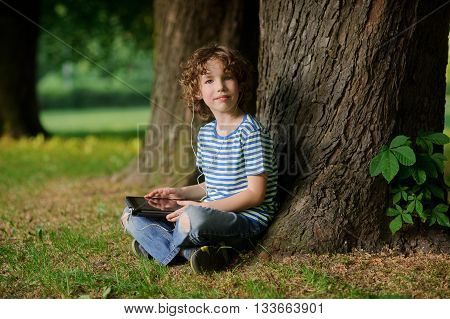 The boy of 8-9 years sits leaning against a tree and holds the tablet in hand. The little fellow with a blond curly hair looks in a camera. In ears earphones. Behind the back there is a thick tree trunk.