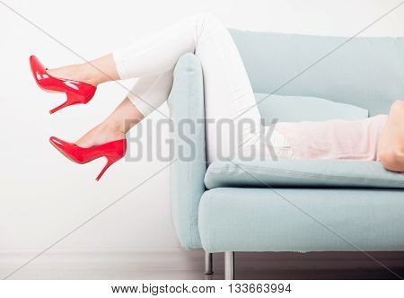 Relaxing Woman And Red High Heels On Sofa At Home