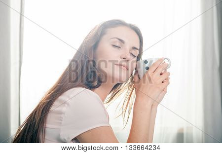 Portrait Of Young Woman Relaxing At Home And Drinking Coffee. Casual Style Indoor Shoot
