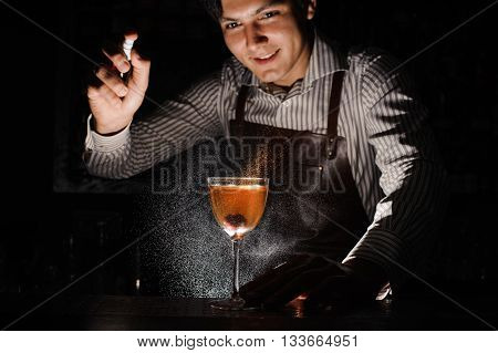 Expert barman is spraying on cocktail at night club