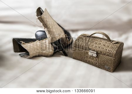 beige shoes and handbag on a white blanket