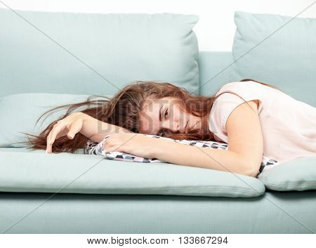 Exhausted Young Woman Lying On Couch At Home. Casual Style Indoor Shoot