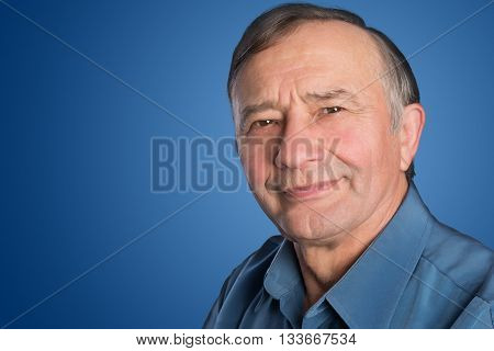 Confident senior male teacher in front of a blank blue background