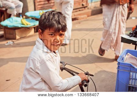 KOLKATA, INDIA - JAN 10, 2016: Unidentified kid on child bicycle driving outdoor in indian city on January 10, 2016. Kolkata's literacy rate of 87.14 perc. exceeds the all-India average of 74 perc.