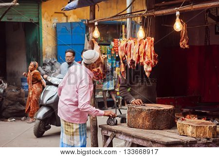 KOLKATA, INDIA - JAN 10, 2016: Elderly man watching on meat market stall of old indian city street on January 10, 2016. Kolkata's literacy rate of 87.14 perc. exceeds the all-India average of 74 perc.