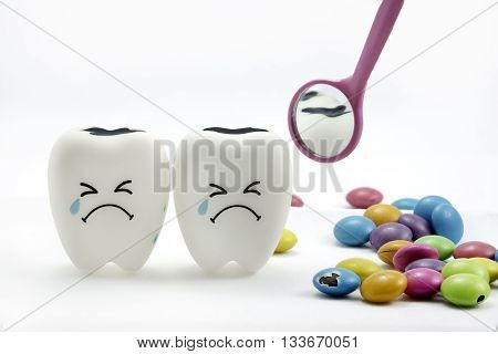 Tooth decay is crying with dental mirror and sugar coated chocolate on the side. On a white background