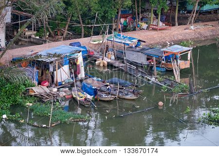 Boats and floating houses in a slum urban area on Sai Gon river. SAI GON, VIET NAM