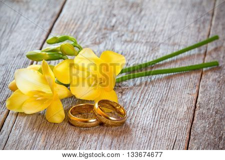 Golden wedding rings with freesia flower on wooden background