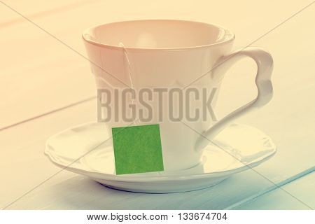 Soft pastel still life with teacup on wooden background