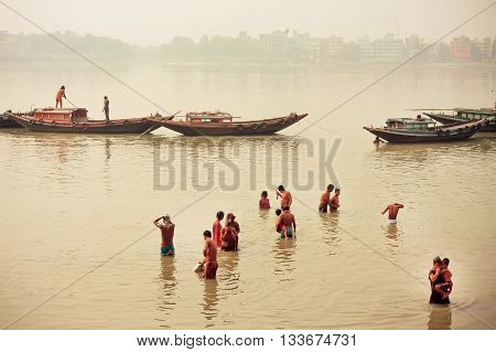 KOLKATA, INDIA - JAN 17, 2016: People bathing in dirty water of indian river past the riverboats on January 17, 2016. Kolkata's literacy rate of 87.14 perc. exceeds all-India average of 74 perc