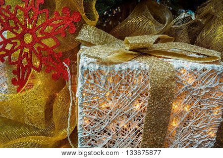 Christmas decorative box with internal warm tungsten lighting, giving the image a warm feel, in among other ornaments. A closeup view.