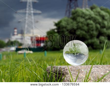Glass ball on concrete, green grass. Background - power lines, stormy sky, cars. The concept - a source of energy, electrification, environment in big cities