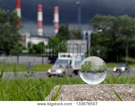 Glass ball on concrete, green grass. Background - pipe heating plant, stormy sky, cars. Concept - gassed cities, smog, harmful emissions into the atmosphere, the environment in big cities