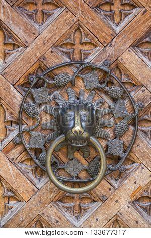 Solid metal knocker on the wooden door.