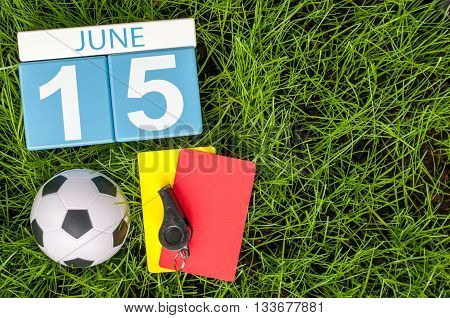June 15th. Image of june 15 wooden color calendar on green grass background with football outfit. Summer day.