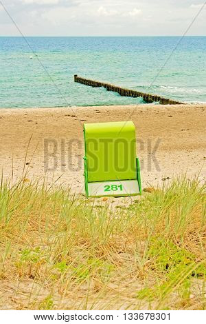 lonely beach chair at beach with ocean baltic sea and wave breaker in the background