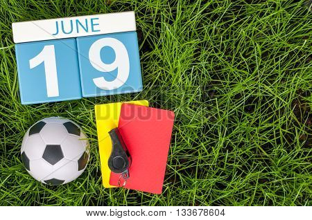 June 19th. Image of june 19 wooden color calendar on green grass background with football outfit. Summer day.