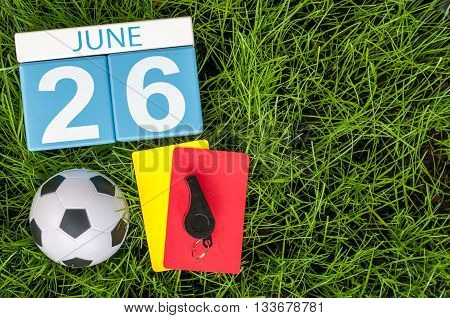June 26th. Image of june 26 wooden color calendar on green grass background with football outfit. Summer day.
