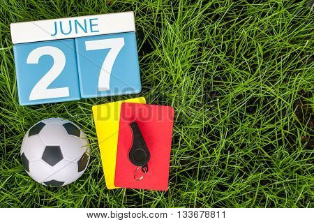 June 27th. Image of june 27 wooden color calendar on green grass background with football outfit. Summer day.