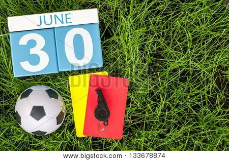 June 30th. Image of june 30 wooden color calendar on green grass background with football outfit. Summer day.