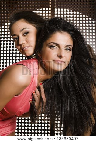 two pretty girlfriends at party dancing smiling close up, fancy fashion dresses creative interior background