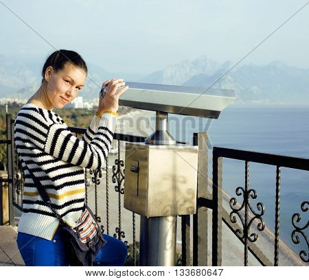 young real woman looking through telescope at sea viewpoint in Ataturk park, sunny morning