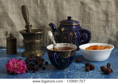 Still life with wild rose flower cup of tea rosehip and dates