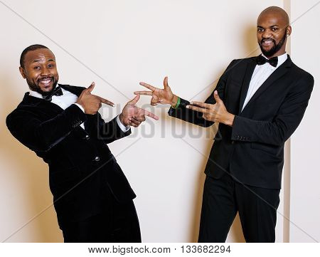 two afro-american businessmen in black suits emotional posing, gesturing, smiling. wearing bow-ties, lifestyle people concept
