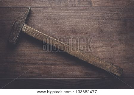 old rusty hammer on the wooden table