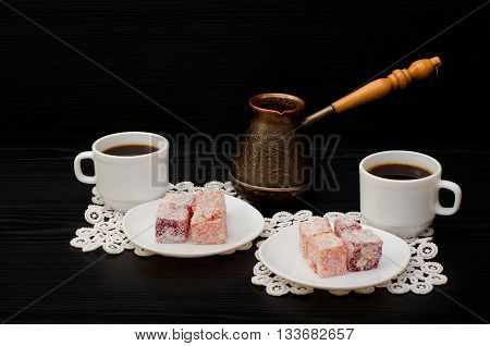 Cezve colorful Turkish Delight and two cups of coffee on the lace napkins black background