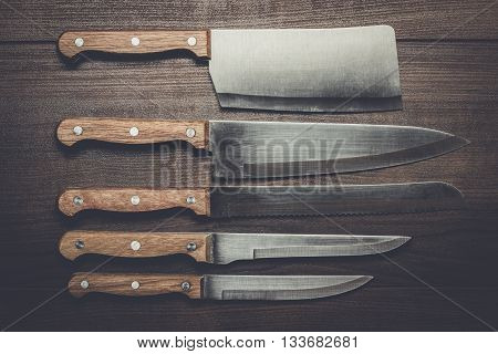 five kitchen knifes over brown wooden table