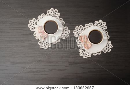 Top view of two mugs of coffee on a saucer with Turkish Delight. Lacy napkins black table. Space for text