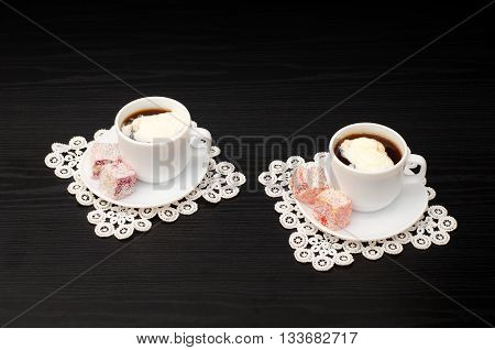 View at an angle into two mugs of coffee with ice-cream Turkish delight on a saucer on white lace napkins. Black background