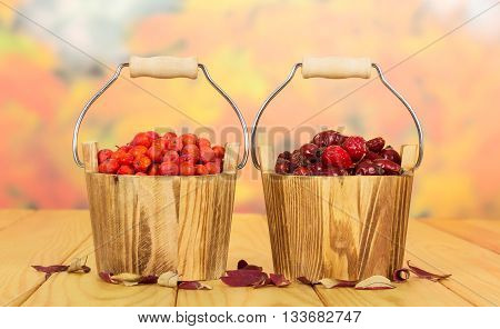 Rowan berries and rose hips in wooden buckets of on a background of autumn leaves.