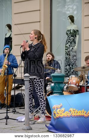 VILNIUS LITHUANIA - MAY 16: Unidentified musician sings and plays guitar in Street Music Day on May 16 2015 in Vilnius. Its a most popular event on May in Vilnius Lithuania
