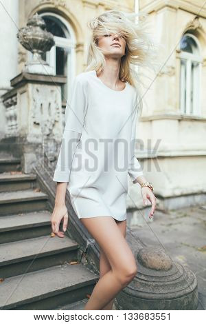 Attractive girl blonde with long hair, in white short dress, down the stairs against of an old house architecture. Dynamic hair in the wind.