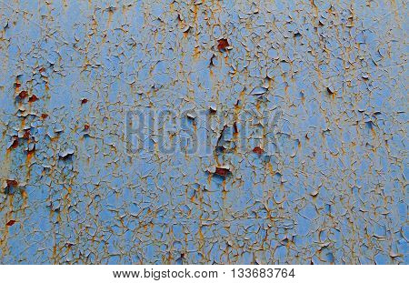 Blue cracked paint on rusty iron wall
