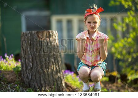 Angry little girl sitting outdoor.