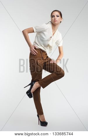 high fashion portrait of young elegant woman. White blouse, brown pants. Studio shot